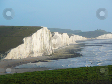 White Cliffs stock photo, Majestic white cliffs on the south UK coast with a lighthouse on the far hill and people enjoying a midday stroll on New Years Day by Helen Shorey