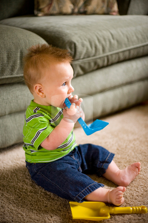 Baby Boy with Toys stock photo, A portrait of a happy baby boy sitting on the floor playing with toys. Shallow depth of field. by Travis Manley