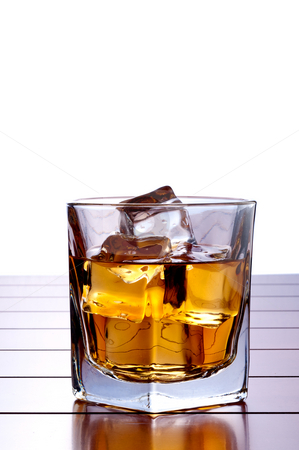 A vertical image of a glass of whiskey with ice on a wooden bar  stock photo, A vertical image of a glass of whiskey with ice on a wooden bar table with a white background and space for copy by Vince Clements
