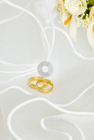 Wedding rings and flowers over veil stock photo, Wedding rings and flowers decorations over bridal veil by Desislava Dimitrova