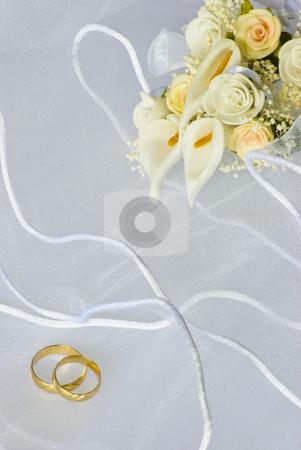 Wedding rings and flowers over veil stock photo, Wedding rings and flowers decorations over bridal veil by Desislava Dimitrova