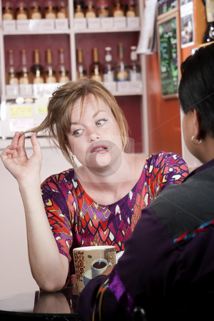 Bored woman in coffee house with male friend stock photo, Bored pretty woman with red hair in coffee house with male friend by Scott Griessel