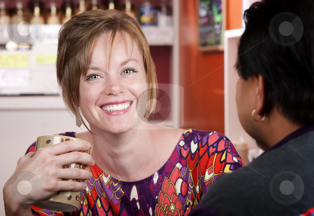 Woman in coffee house with male friend stock photo, Pretty woman with red hair in coffee house with male friend by Scott Griessel