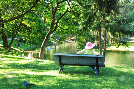 Woman in the park. stock photo, An woman with a big pink hat sitting on a bench in a big park in front of an pond in beautiful sunshine. by Horst Petzold