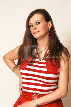 Woman in red dress. stock photo, Pretty woman with long brown hair sitting on a chair for a portrait in an red dress for light beige background and looking in the camera. by Horst Petzold