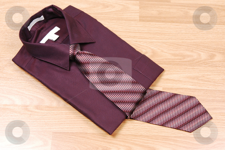 Burgundy dress shirt with tie. stock photo, Burgundy dress shirt on a wood surface with an burgundy and beige tie for sale in the store. by Horst Petzold