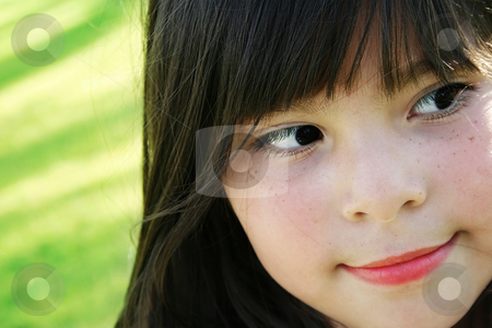 Cute girl stock photo, Close up shot of cute mixed race girl over grass background, focus on face by iodrakon