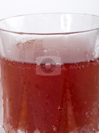Red carbonated drink in frosted crystal glass closeup stock photo, Closeup of frosted glass with red drink and bubbles by Jeff Cleveland