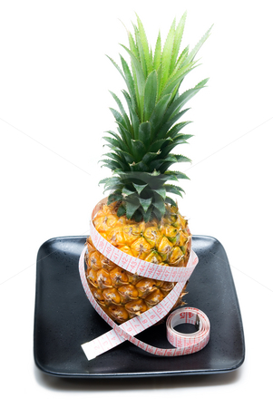 Pineapple stock photo, Ripe vivid pineapple on a black plate with tape meter by Francesco Perre