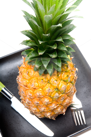 Pineapple stock photo, Ripe vivid pineapple on a black plate with knife and fork by Francesco Perre