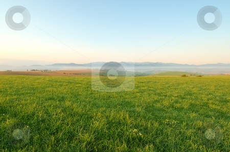 Meadow in morning stock photo, Meadow in morning with mountains in background by Juraj Kovacik