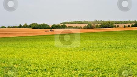 Tractor stock photo, Tractor working on farm fields in spring by Juraj Kovacik