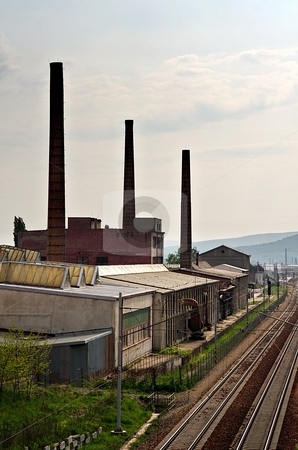 Factory stock photo, Old factory with chimneys and railroad with pink sky by Juraj Kovacik
