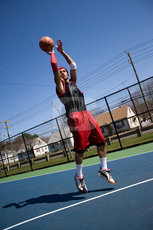 Basketball Player Shooting stock photo, A young basketball player shooting a three point jump shot. by Todd Arena