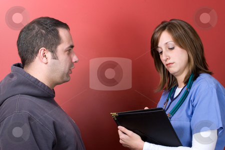 Worried Patient at the Doctors stock photo, A young nurse talks to a concerned patient during his visit. by Todd Arena
