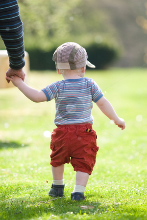 Trust stock photo, A little boy is lead by his parent walking over grass by Jan Martin Will