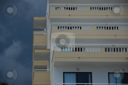 Apartment building stock photo, Apartment building agains the dark cloudy sky by Wolfgang Zintl