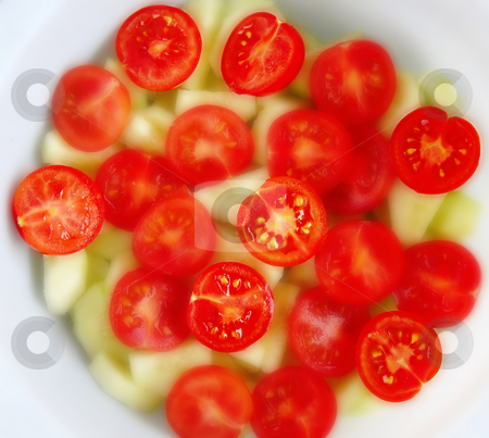 Cherry tomatoes salad stock photo, Red cherry tomatoes cut salad with cucumber by Julija Sapic