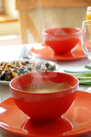 Dinner stock photo, Red plates with hot soup served on table in kitchen for dinner by Julija Sapic