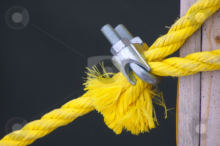 Lashing stock photo, A yellow rope for a tie-down is clamped by metallic fastening by Sergej Razvodovskij