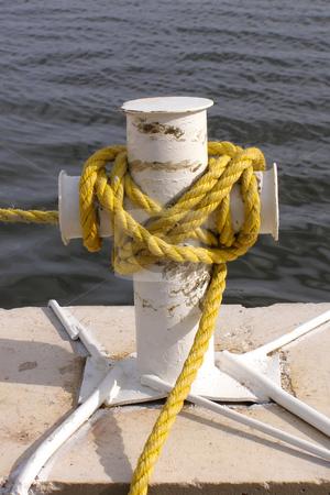 Bollard stock photo, Yellow rope on the bollard by Sergej Razvodovskij