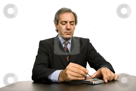 Working stock photo, Mature business man on a desk, isolated on white by Rui Vale de Sousa