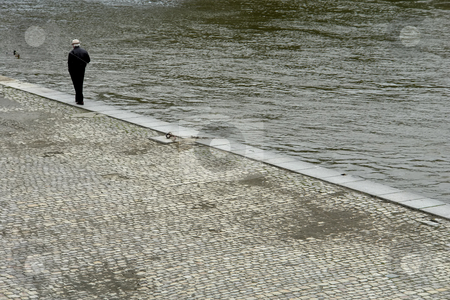 Walking stock photo, Old man walking along the river in prague by Rui Vale de Sousa