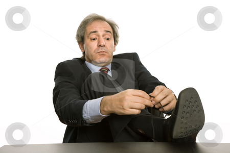Tying stock photo, Mature business man tying his shoe in a desk by Rui Vale de Sousa