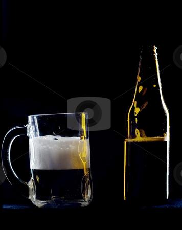 Beer mug and bottle stock photo, A beer mug sits half full next to a beer bottle by Matt Baker