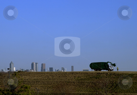 Looking at the city stock photo, A garbage collector standing on a landfil looks out to the Atlanta skyline by Matt Baker