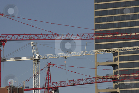 Construction cranes stock photo, Three cranes operate during the construction of a building by Matt Baker