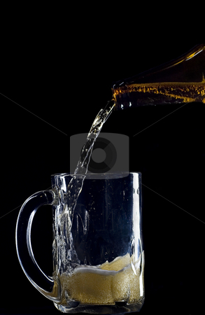 Pouring beer stock photo, Pour a beer bottle into a glass mug by Matt Baker