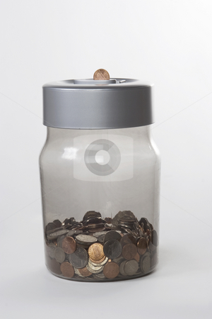 Money jar stock photo, An isolated money jar full of coins by Matt Baker