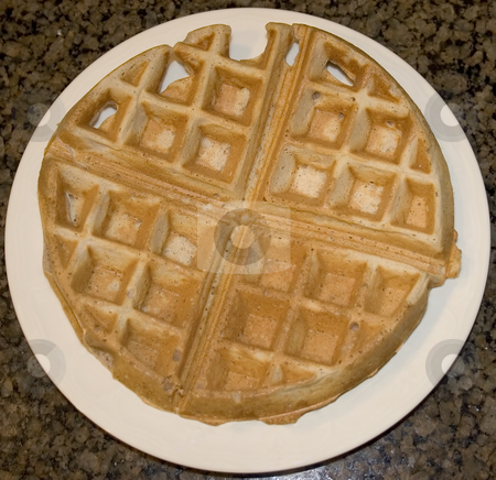 Waffle on plate stock photo, A ready to eat waffle sits on a white plate by Matt Baker