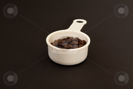 Cup of coffee beans stock photo, A coffee bean is the seed of the coffee plant (the pit inside the red or purple fruit). The fruits, coffee cherries or coffee berries, most commonly contain two stones with their flat sides together. by Mariusz Jurgielewicz