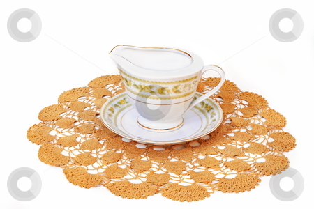 Fine China stock photo, Fine China gravy server  on hand crafted doily isolated on white background by Jack Schiffer
