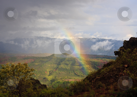 Rainbow over Waimea Canyon on Kauai stock photo, Rainbow behind craggy rocks in Waimea Canyon on Kauai by Steven Heap