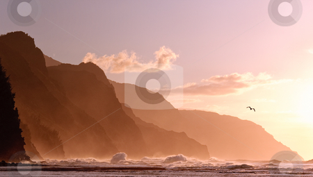 Sunset off the Na Pali coastline on Kauai with a stormy sea stock photo, Receding headlands of Kauai coastline illuminated at sunset over a stormy sea with a distant bird by Steven Heap