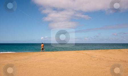Sea fisherman on an empty beach stock photo, Rear view of fisherman on a wide sandy beach by Steven Heap