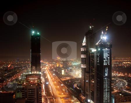 Cityscape of Dubai stock photo, Towering city skyscraper blocks in Dubai at night by Steven Heap