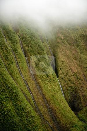 Multiple waterfalls on Kauai stock photo, Several waterfalls streaming down the rock face in Kauai by Steven Heap