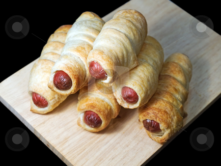 Hot dogs stock photo, Heap of hot dogs in pastry isolated ona a black background. by Sinisa Botas