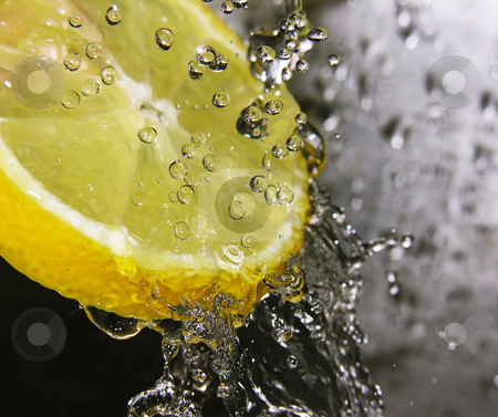 Refreshing lemon stock photo, Water drops falling onto a lemon - focus is on the water drops by Kirsty Pargeter