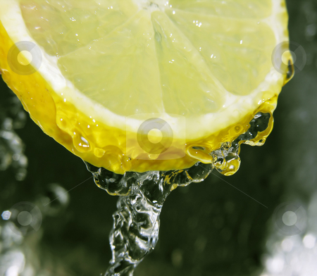 Refreshing lemon stock photo, Water dripping off a lemon slice by Kirsty Pargeter