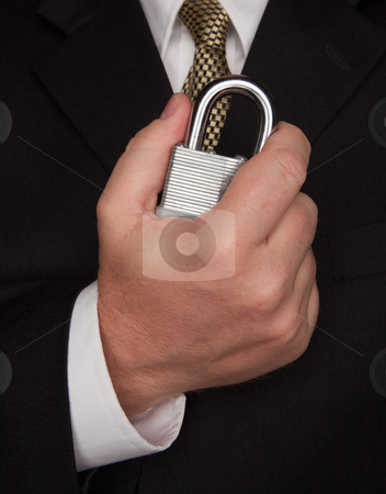 Businessman Holding Large Lock stock photo, Businessman with Coat and Tie Holding Large Lock. by Andy Dean