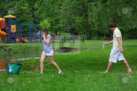 Couple cleaning up the park stock photo, Couple showing how it can be fun to clean up a park together. by Chris Torres