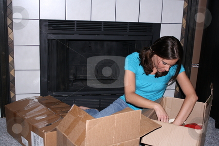 Boxes from the attic stock photo, Girl goes through boxes from the attic. by Chris Torres