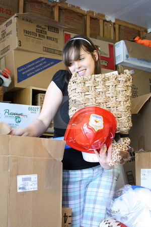 Girl surrounded by boxes stock photo, A girl surrounded with boxes trying to sort through the items. by Chris Torres