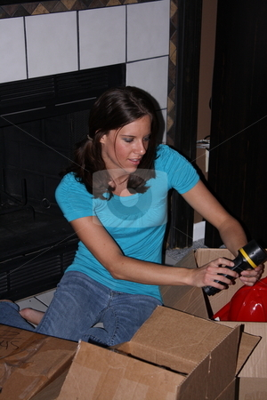 Girl organizing boxes stock photo, Girl sorting through boxes. by Chris Torres