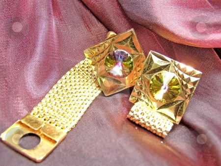 Gold sleeve-link stock photo, Gold sleeve-links against red fabric background by Sergej Razvodovskij